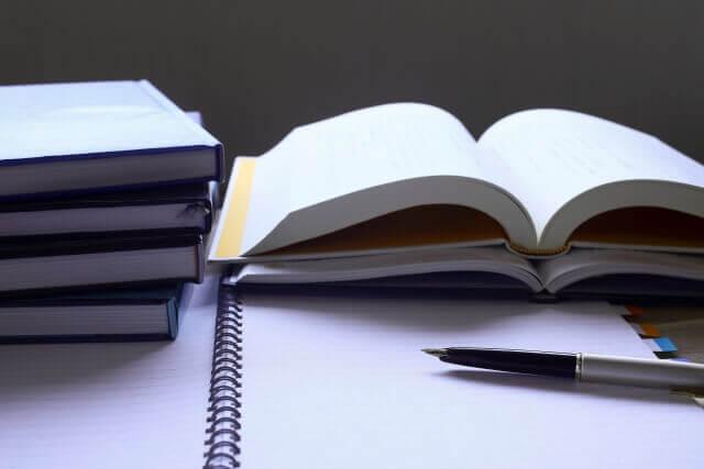 積まれた本と書きかけのノート