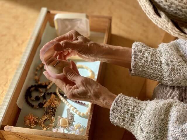 指輪の箱を持つ高齢者の手