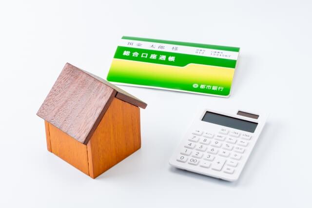 家の模型と通帳と電卓